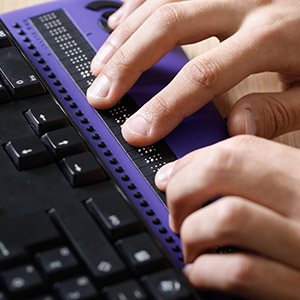 Visually impaired person using braille keyboard