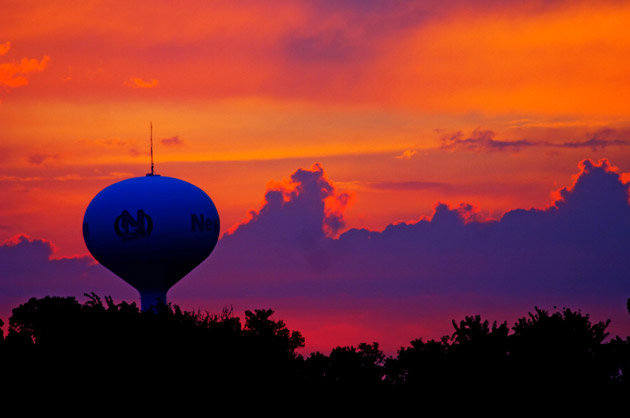 Large water tower in the distance during an orange and purple sunseti in Newton KS