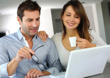 Happy couple looking to sell their home researching on a laptop