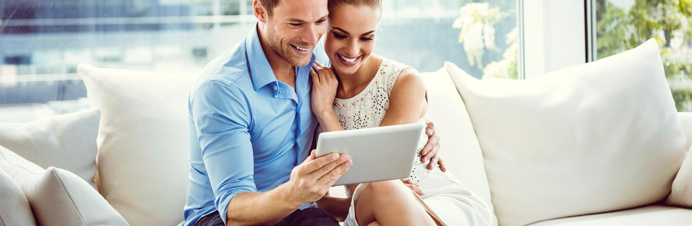 happy couple searching for luxury homes on a tablet