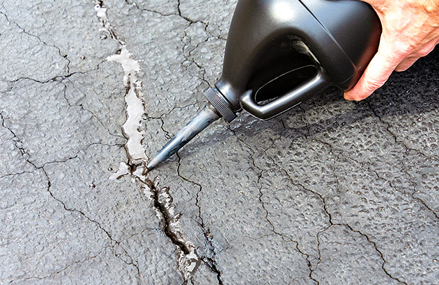 Close up of person filling driveway cracks with a special device