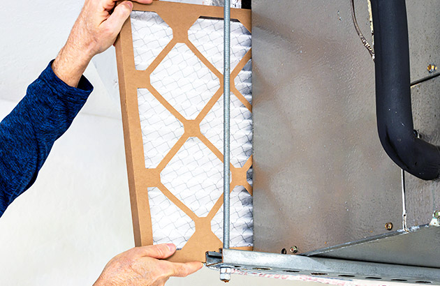 Close up of person installing new air filter into HVAC unit