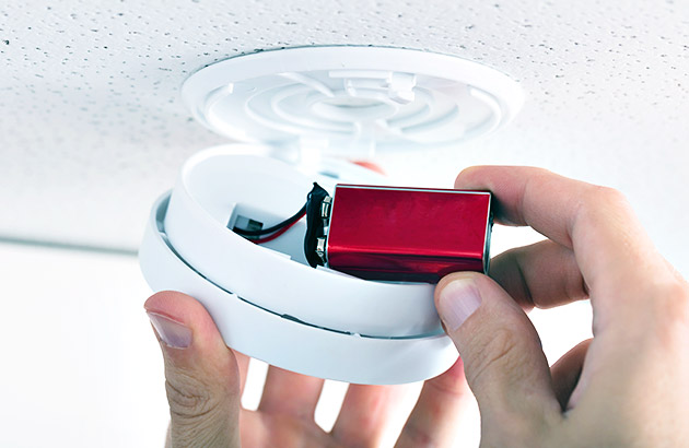 Close up of a person installing a new battery into a smoke detector