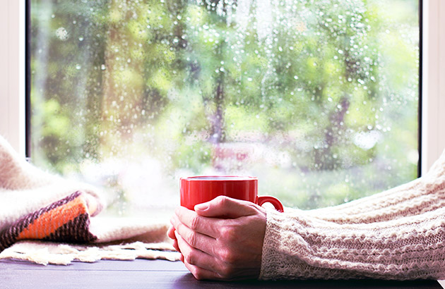 Close up of womain holding a cup of hot coffee by a window on a rainy day