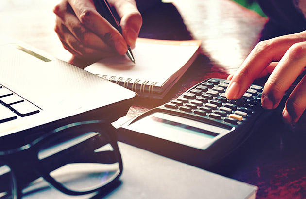 Macro focused photo showing person using calculator and taking notes