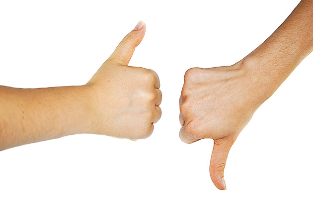 Two hands, one showing a thumbs up and one showing a thumbs down