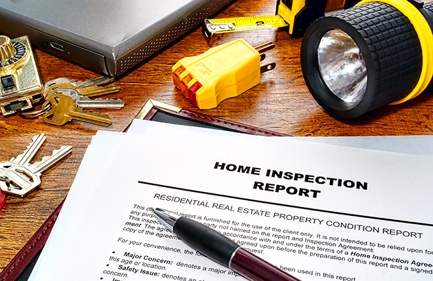 Home inspection report on the table next to keys, flashlight, tape measure