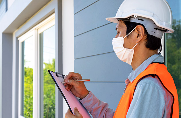 Home inspector wearing mask, hard-hat and safety vest, writing a note on a clipboard