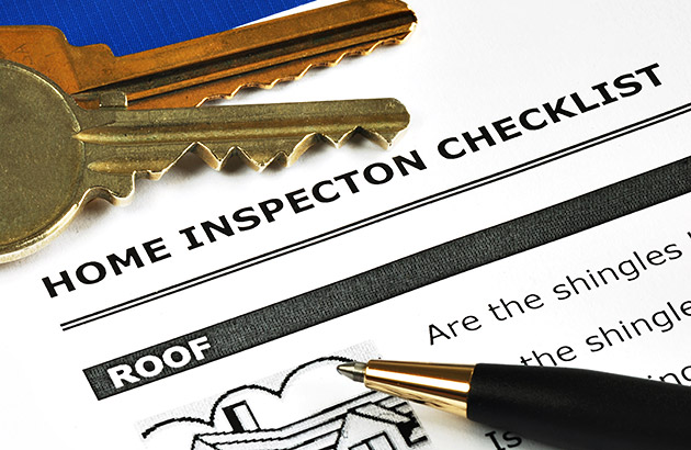 Close-up of a document titled Home Inspection Checklist with a pen and two keys on top