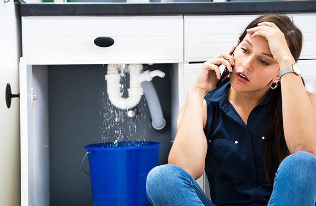 A stressed woman on the phone with leaking bathroom plumbing in the background