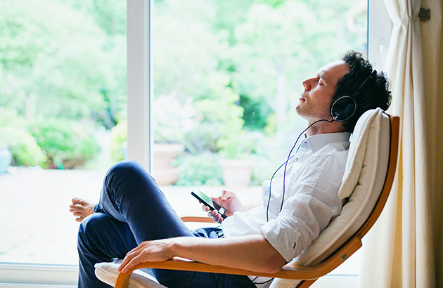 A man relaxing in a chair listening to music on headphones holding a smartphone