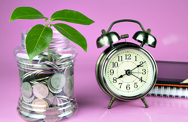Plant growing out of coins in jar next to alarm clock