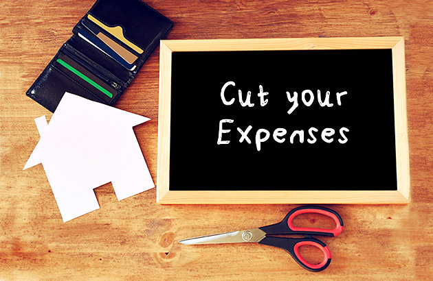 Concept with chalk board with cut your expenses written next to scissors and wallet
