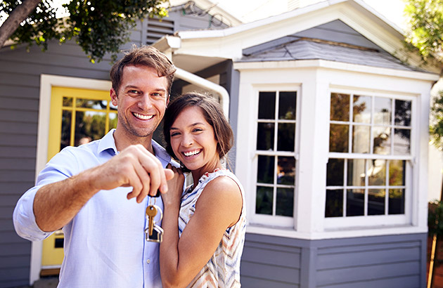 Happy young couple holding keys to their new house