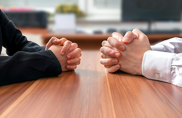 Zoom on hands on table of two people facing one another