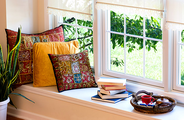 A classic style window seat with intricate pillows, books and a coffee serving tray