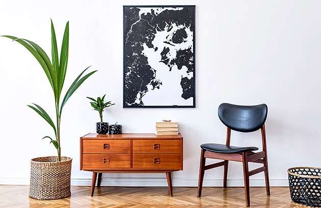 A small table with drawers next to an indoor plant and mid-century chair
