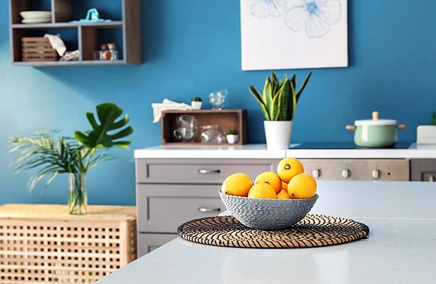 A modern kitchen with a basket of lemons on a light sleek countertop
