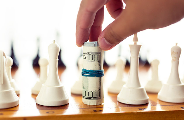 Concept of money management strategy showing a roll of cash in place of a chess piece on chess board