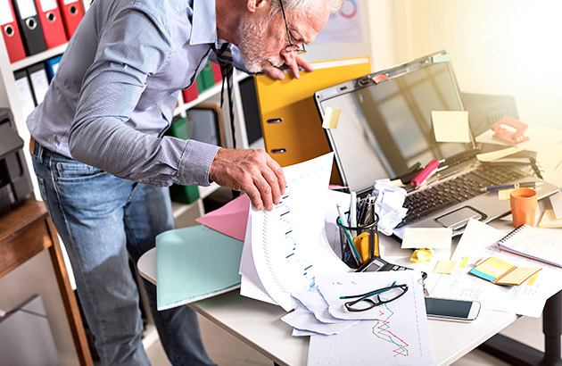 Older man searching through a cluttered desk