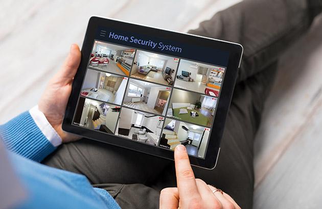 Homeowner looking at security camera views from tablet