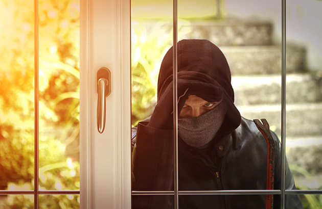 A burglar peering into home through window from the outside