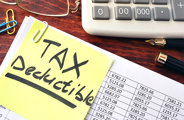 A close up of a financial document with Tax Decuctible on a post it note on top