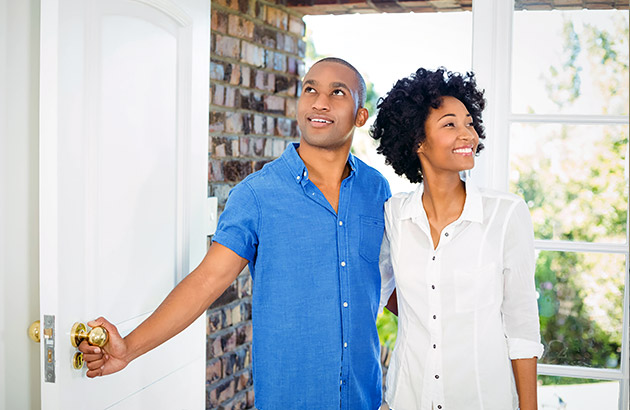 Happy potential home buyers walking through front door
