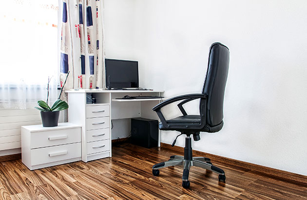 A small office with a comfortable chair and functional desk with drawers