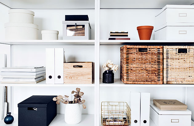 Clean white storage shelves with various stylish storage boxes neatly placed