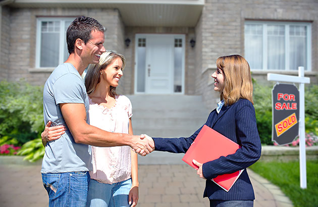 A happy couple with a real estate agent in front of a sold house