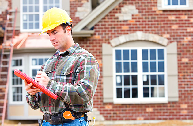 A home inspector taking notes outside of a home