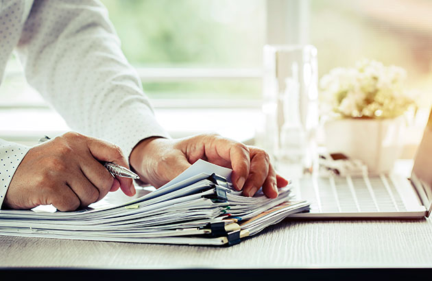 Homeowner reviewing stack of neatly organized paper records