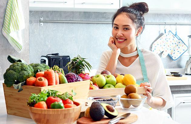 A happy woman preparing fresh fruits and veggies at home