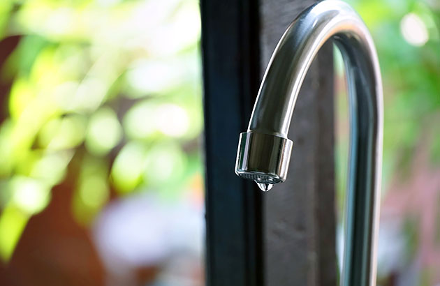 Close up of a dripping kitchen faucet