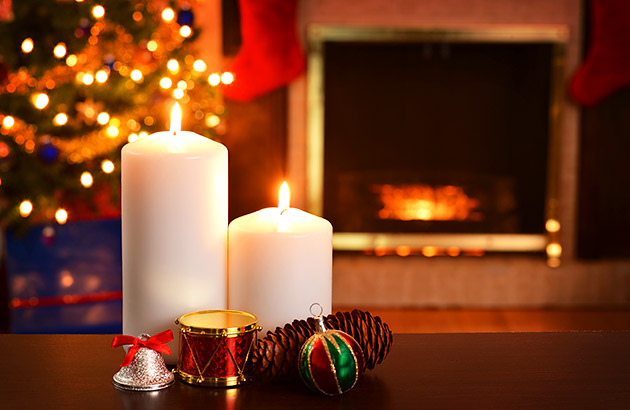 A relaxing living room lit with candles and a Christmas tree in the background