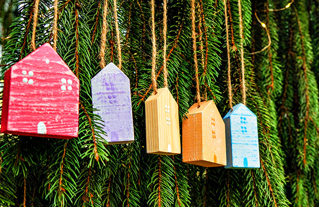 Vintage multi-colored wood ornaments hanging natural pine tree branches