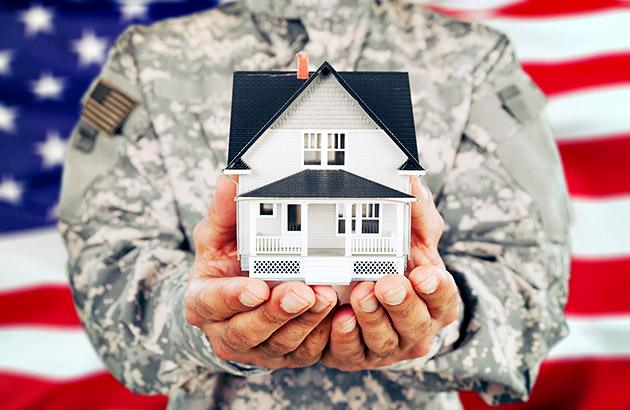 An armed-services member holding a model house