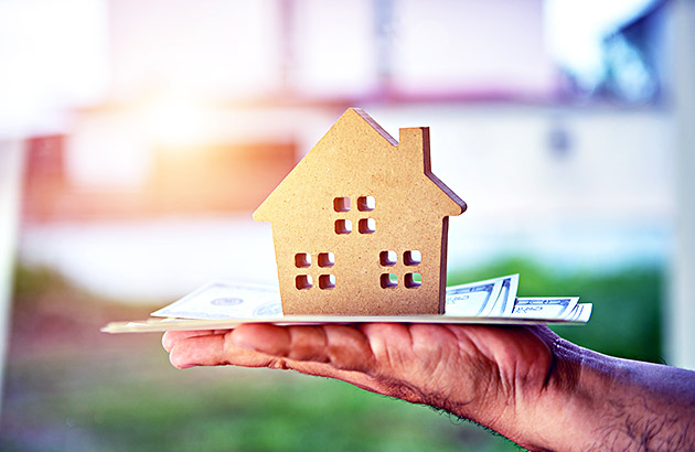 Home equity concept - hand holding model house and cash