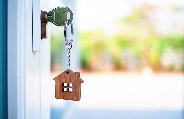 Key with wooden house keychain in open door