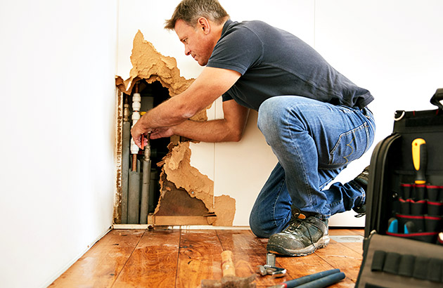 Contractor repairing pipes through damaged wall