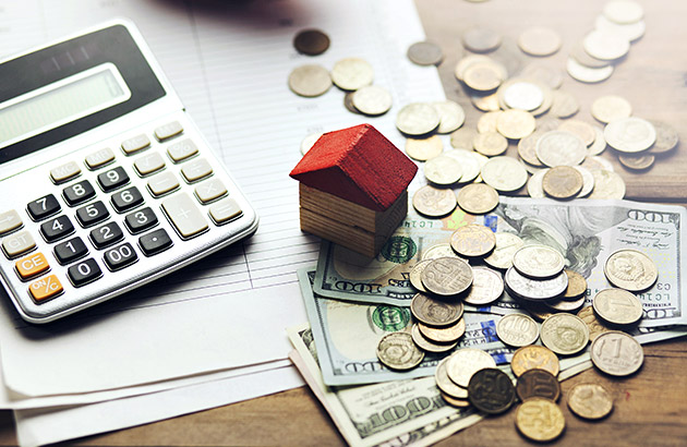 Concept of calculating the costs of selling with model house, cash and calculator