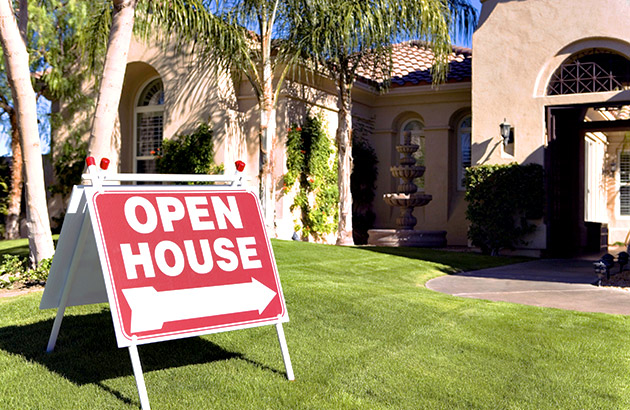 Open house sign outside a beautiful stucco home with an immaculate front landscape