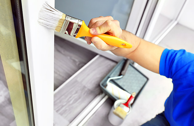 Homeowner painting wooden trim of outside window