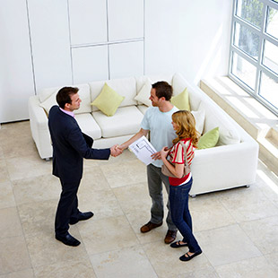 A couple shaking hands with a REALTOR at an Open House in the Cowley area